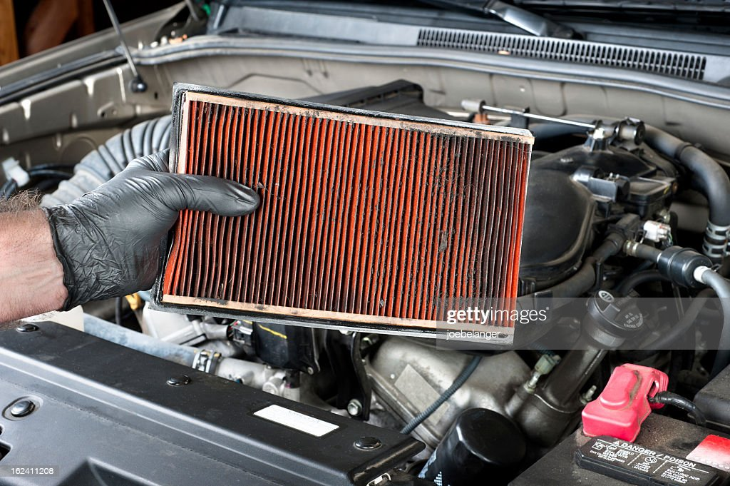 Removing a dirty automotive air filter : Stock Photo