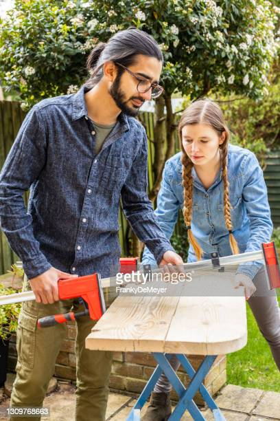 removing clamps from recycled wood. young multi-ethnic couple running a home woodworking furniture business together - repairing stock pictures, royalty-free photos & images