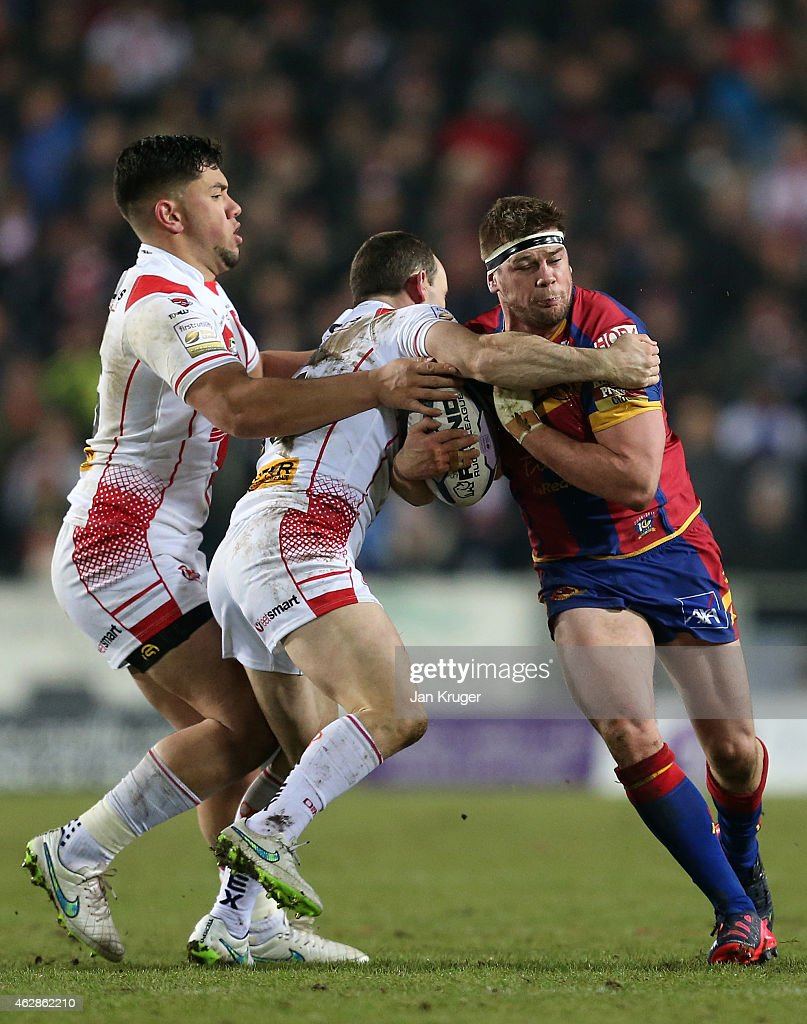 Remy Casty of Catalans Dragons is tackled by Lance Hohaia and Andre Savelio of St Helens during the First Utility Super League match between St Helens and Catalans Dragons at Langtree Park on February 6, 2015 in St Helens, England.