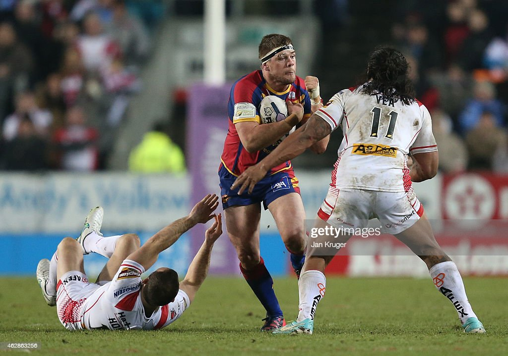 Remy Casty of Catalans Dragons is tackled by Lance Hohaia and Atelea Vea of St Helens during the First Utility Super League match between St Helens and Catalans Dragons at Langtree Park on February 6, 2015 in St Helens, England.