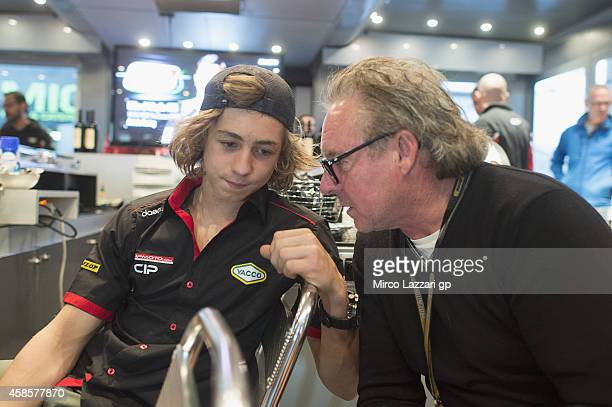 Remy Gardner of Australia speaks with his father during the presentation of the new 2015 season of Team CIP in hospitality during the MotoGP of...
