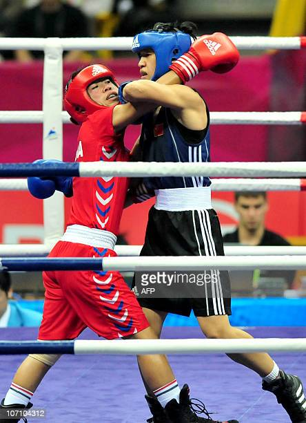 Ren Cancan of China competes against Chungneijang Mary Kom Hmangte of India in the women's 4851kg boxing semifinal competition at the 16th Asian...