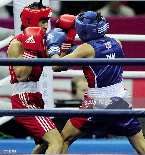 Ren Cancan of China competes with Annie Albania of Philippines during the women's 4851kg boxing final competition at the 16th Asian Games in...