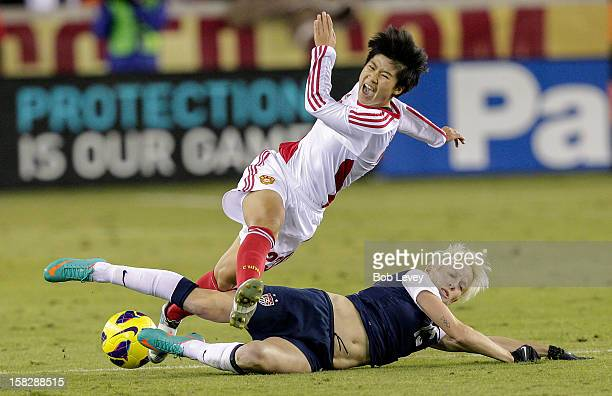 Ren Guixin of China is upended by Megan Rapinoe of the United States in the second half at BBVA Compass Stadium on December 12, 2012 in Houston,...