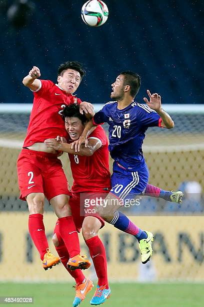 Ren Hang of China and Cai Huikang of China compete for the ball against Kengo Kawamata of Japan during men's EAFF East Asian Cup 2015 match between...