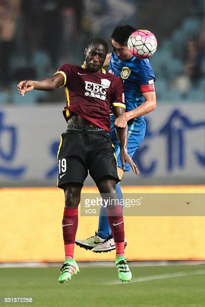Ren Hang of Jiangsu Suning and Jacob Mulenga of Shijiazhuang Ever Bright compete for the ball during the Chinese Football Association Super League...