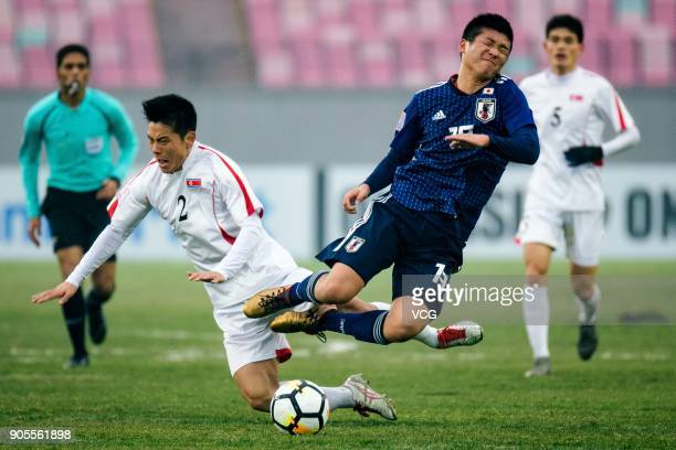 Ren Komatsu of Japan and An Song-Il of North Korea compete for the ball during the AFC U-23 Championship Group B match between Japan and North Korea...