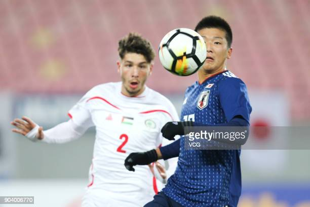 Ren Komatsu of Japan and Michel Termanini of Palestine compete for the ball during the AFC U23 Championship Group B match between Japan and Palestine...