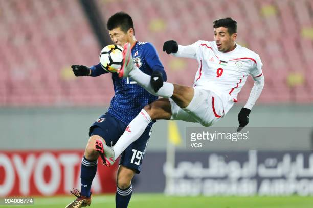Ren Komatsu of Japan and Oday Dabbagh of Palestine compete for the ball during the AFC U23 Championship Group B match between Japan and Palestine at...