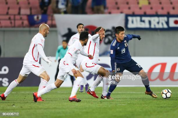 Ren Komatsu of Japan is challenged by players of Palestine during the AFC U23 Championship Group B match between Japan and Palestine at Jiangyin...