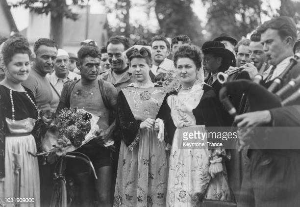 René Vietto toujours maillot jaune est entouré de jeunes bretonnes en costume régional à son arrivée à Vannes en 1947 en France