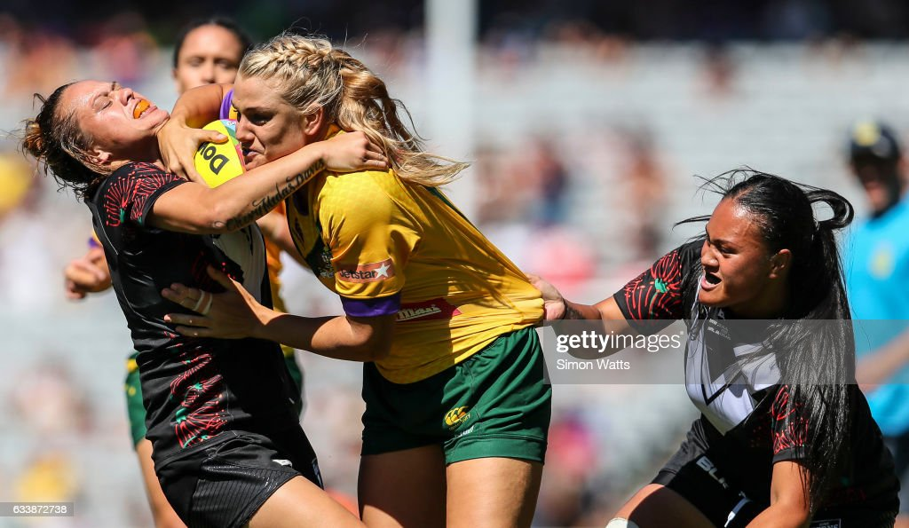 Renae Kunst of the Jillaroos is tackled by Amber Kani (L) and Lilieta Maumau of the Black Ferns during the 2017 Auckland Nines match between the Australian Jillaroos and the Kiwi Ferns at Eden Park on February 5, 2017 in Auckland, New Zealand.