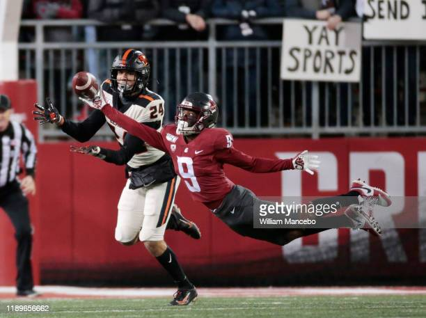 Renard Bell of the Washington State Cougars attempts to catch a pass against David Morris of the Oregon State Beavers in the first half at Martin...