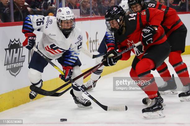 Renata Fast of Canada battles for the puck with Kendall Coyne Schofield of the United States during the first period at Little Caesars Arena on...