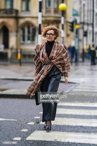 Renata Razdzyk wears glasses, a black turtleneck pullover, a brown checked oversized dress, black leather pants, during London Fashion Week Fall...