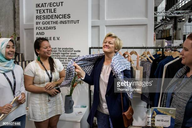 Renate Kuenast of the German Greens Party tests a shawl at Greenshowroom trade show during the MercedesBenz Fashion Week Berlin Spring/Summer 2018 at...