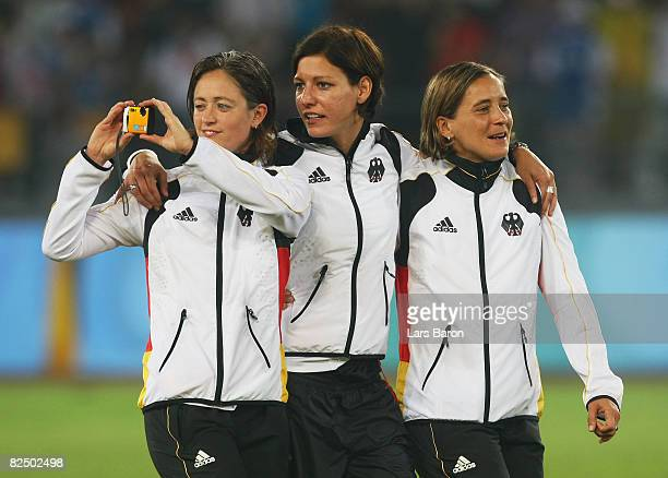 Renate Lingor Linda Bresonik and Sandra Smisek of Germany celebrate prior to receiving their Bronze medals for the Women's Football on Day 13 of the...