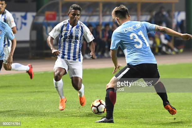Renatinho of Guangzhou RF and Yang Shanping of Dalian Yifang compete for the ball during the 2018 Chinese Football Association Super League second...