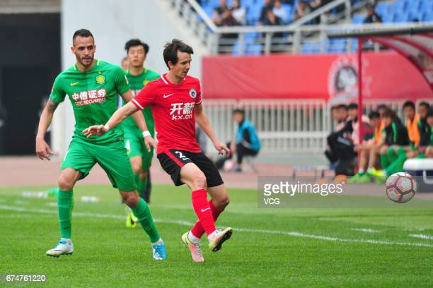 Renato Augusto of Beijing Guoan and Robbie Kruse of Liaoning Kaixin compete for the ball during the seventh round match between Liaoning Kaixin and...