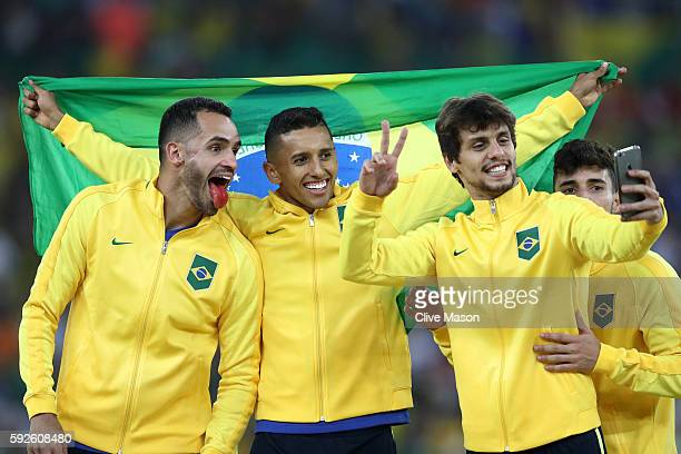 Renato Augusto of Brazil Marquinhos of Brazil and Rodrigo Caio of Brazil celebrate with their medals following the Men's Football Final between...