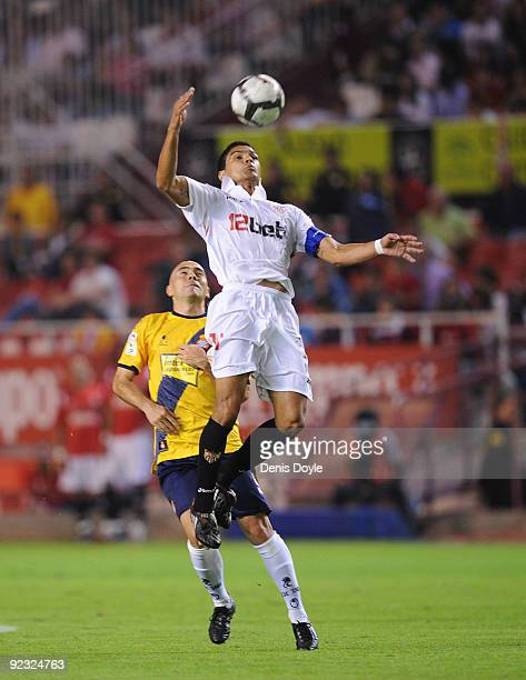 Renato Dirnei of Sevilla heads the ball ahead of Ivan de la Pena of RCD Espanyol during the La Liga match between Espanyol and Sevilla at Estadio...