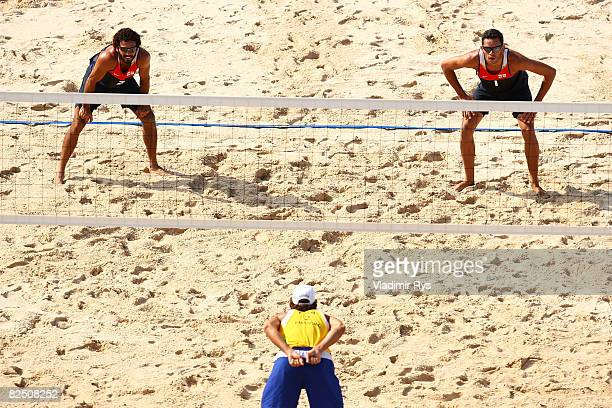 Renato Gomes and Jorge Terceiro of Georgia wait to receive a serve as Emanuel Rego of Brazil calls a serve during the bronze medal beach volleyball...