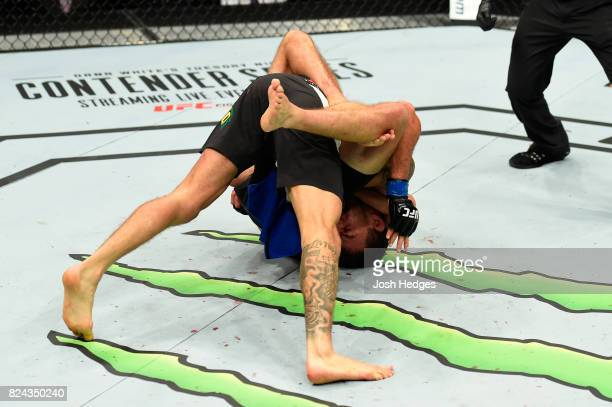 Renato Moicano of Brazil taps out against Brian Ortega after being caught in a choke hold in their featherweight bout during the UFC 214 event at...