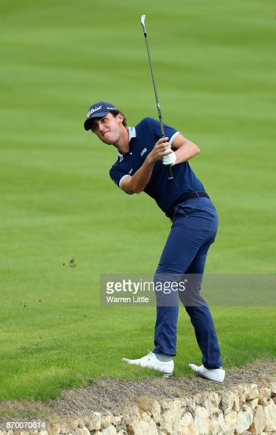Renato Paratore of Italy plays his second shot into the 18th green from the edge of the pond during the third round of the Turkish Airlines Open at...