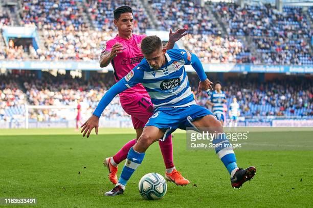Renato Santos of Malaga CF competes for the ball with Francisco Montero of Deportivo de La Coruna during the La Liga Smartbank match between...
