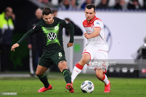 Renato Steffen of VfL Wolfsburg competes for the ball with Kevin Stoeger of Fortuna Duesseldorf during the Bundesliga match between VfL Wolfsburg and...