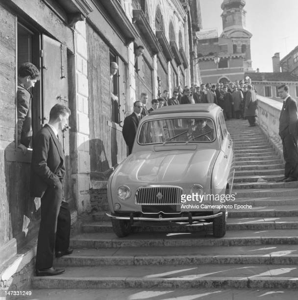 A Renault 4L car getting down the stairs of Rialto Bridge Venice 1961