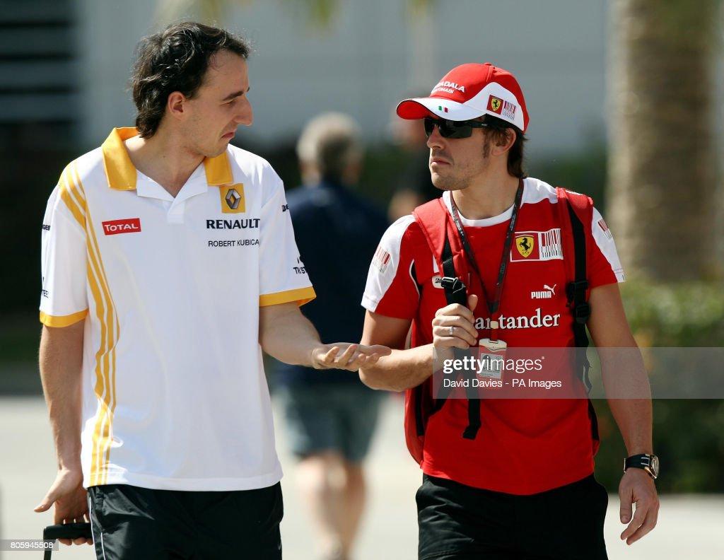 Renault driver Robert Kubica (left) arrives with Ferrari driver Fernando Alonso before Qualifying at the Bahrain International Circuit in Sakhir, Bahrain.