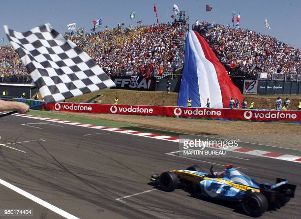 Renault Spanish driver Fernando Alonso waves as he crosses the finish line of the MagnyCours racetrack during the Grand Prix of France 03 July 2005...
