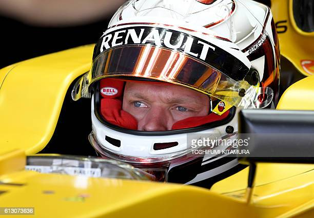 Renault Sport F1 Team's Danish driver Kevin Magnussen watches the video screen in his pit during the first free practice session at the Formula One...