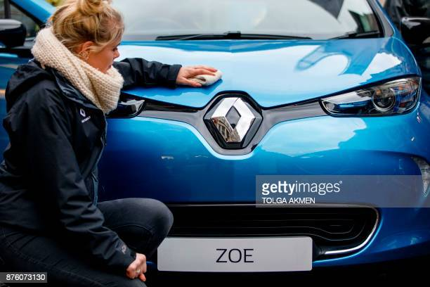 A Renault staff member poses for a photograph while cleaning a Renault Zoe electric vehicle during the Regent Street Motor in London Show on November...