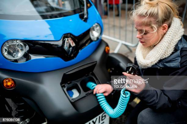A Renault staff member poses for a photograph with the charging cable of a Renault Twizy during the Regent Street Motor Show in London on November 4...