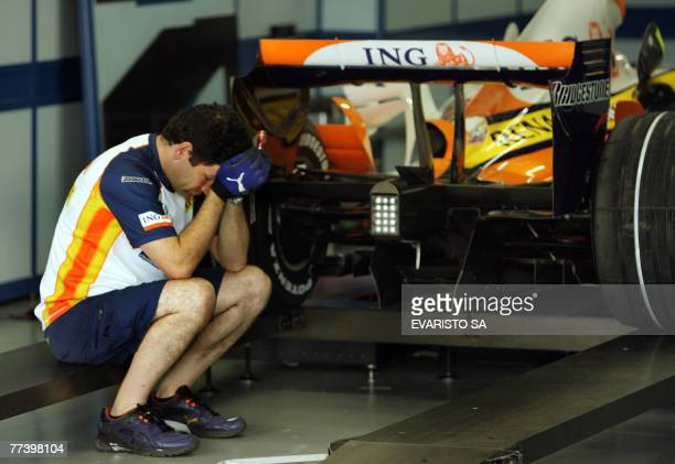 Renault team member awaits for the FIA inspection 18 October 2007 in the pits of the Interlagos racetrack in Sao Paulo, Brazil during the...
