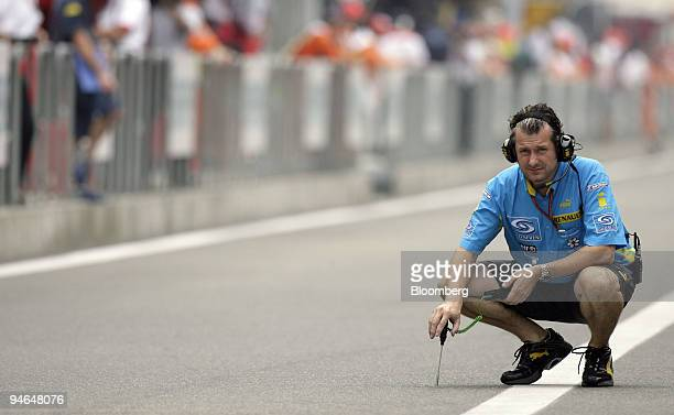 Renault team member measures the track temperature during the first practise day of the Formula 1 Grand Prix of China in Shanghai China Friday...