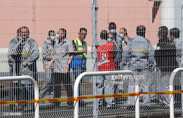 Renault workers and union representatives wearing protective face masks gather at the main entrance of the Renault plant on May 29 2020 in...