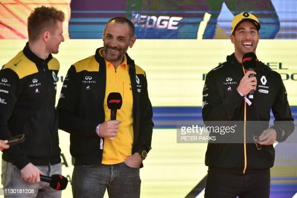 Renault's Australian driver Daniel Ricciardo and German driver Nico Hulkenberg share a laugh with team principal Cyril Abiteboul during an F1 live...