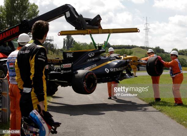 Renault's British driver Jolyon Palmer looks on as his racing car is lifted off the racetrack after a tyre blowout during a practice session at the...