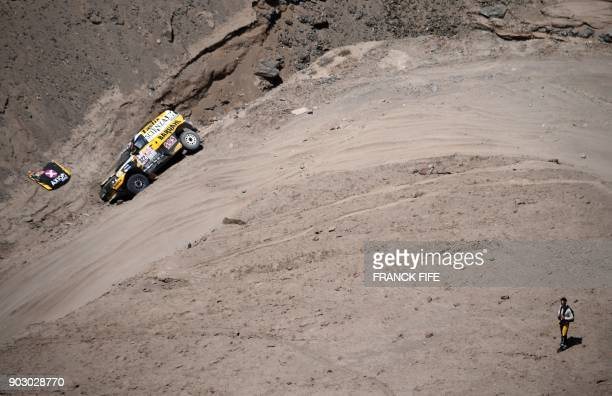 Renault's codriver Santiago Hansen of Argentina reacts next to a car after a crash during Stage 4 of the Dakar 2018 in and around San Juan De Marcona...