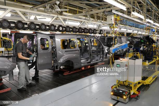 A Renault's employee works on a Kangoo's assembly line during a presidential visit at the Renault factory in Maubeuge northern France on November 8...