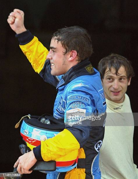 Renault's Fernando Alonso of Spain celebrates his third place win while teammate Jarno Trulli of Italy looks on after the finish of the Malaysian...