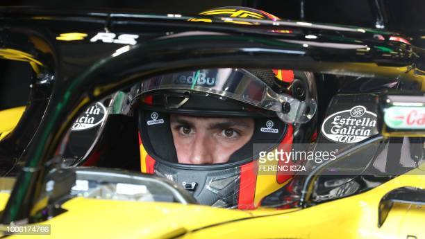 Renault's Spanish driver Carlos Sainz Jr sits in his car during the practice session of the Formula One Hungarian Grand Prix at the Hungaroring...