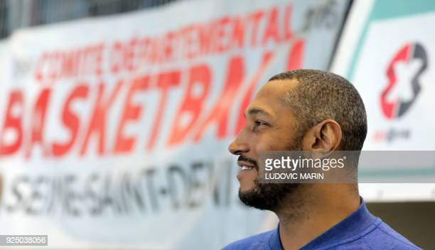 rench basketball player Boris Diaw looks on as French President Emmanuel Macron watches a display of basketball skills during a visit at the Jesse...