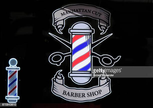 A rendering of an iconic barber's pole is painted on the front window of a barber shop in Midtown Manhattan New York City