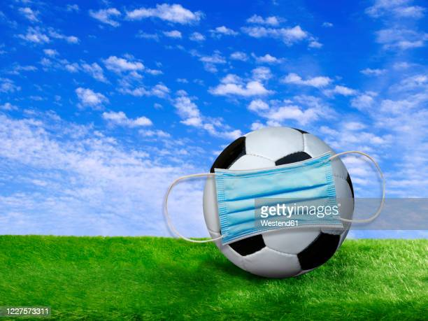 3d rendering, soccer ball covered by surgigal mask on soccer field - audience free event stock pictures, royalty-free photos & images