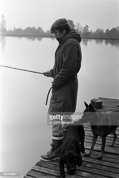 Rendezvous With Alain Delon For Its 41St Birthday Plan de profil d'Alain DELON en bottes canadienne et casquette pêchant dans le lac artificiel de sa...