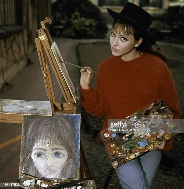 Rendezvous With Anna Karina. Paris - Juin 1964 - Dans son jardin du Trocadéro, devant un chevalet, portant un pull rouge et un chapeau noir,...